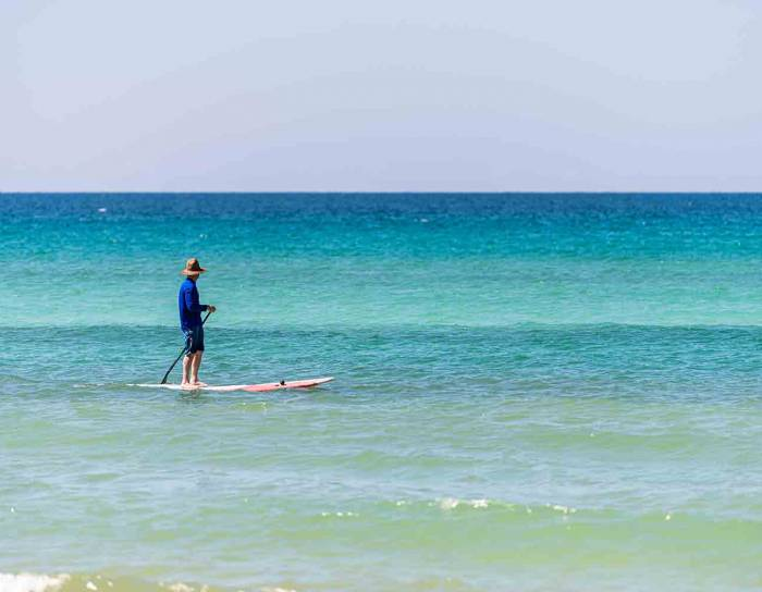 Man in the water with a paddle board