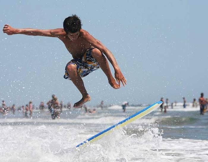 Teenager doing an ollie on a skim board in the water